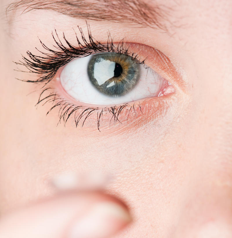 Close up of inserting a contact lens in female eye stock photography