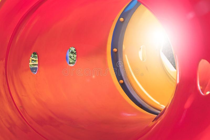 Close up inside colorful tunnel slider with sunlight in playground at public park. Selective focus royalty free stock photography