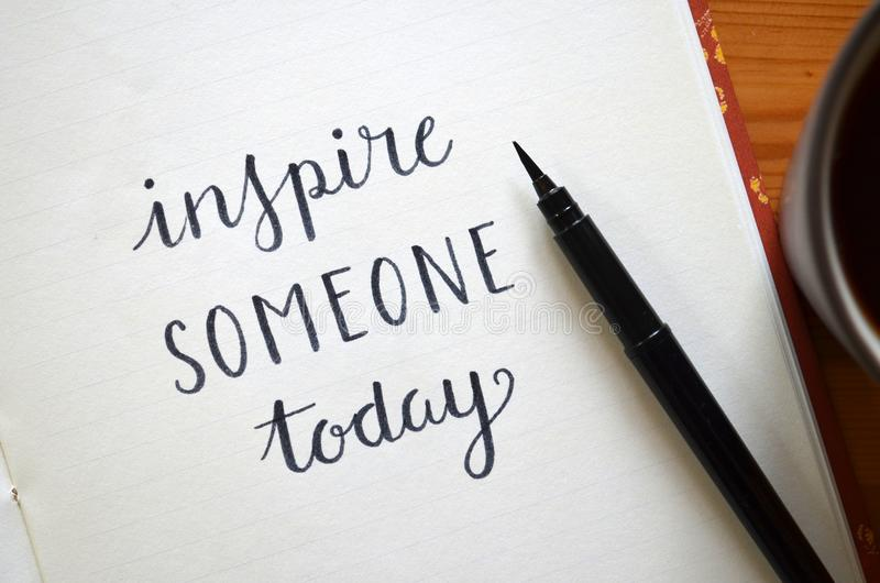 `INSPIRE SOMEONE TODAY` brush calligraphy in notebook royalty free stock photography