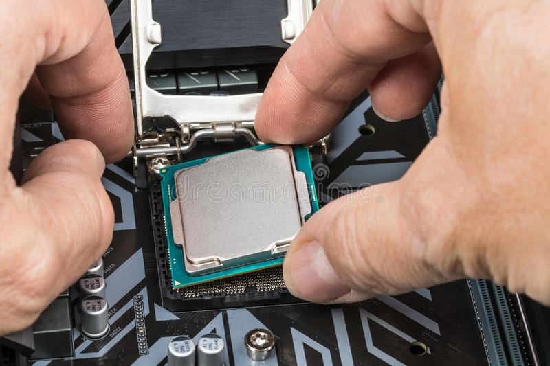 Detail of expert hands at processor replacement royalty free stock photography