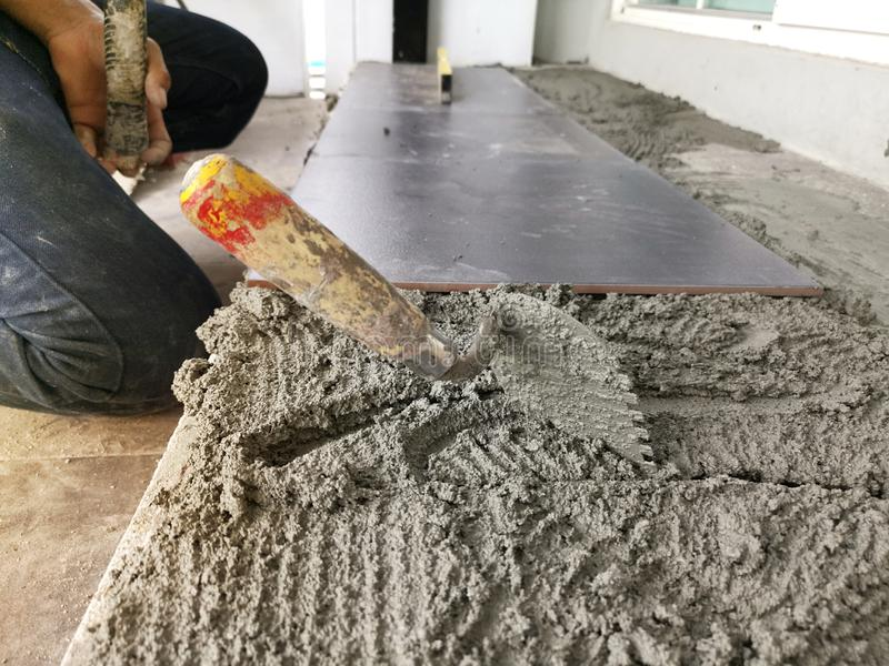 Close-up Installing tiles floor in construction work stock images