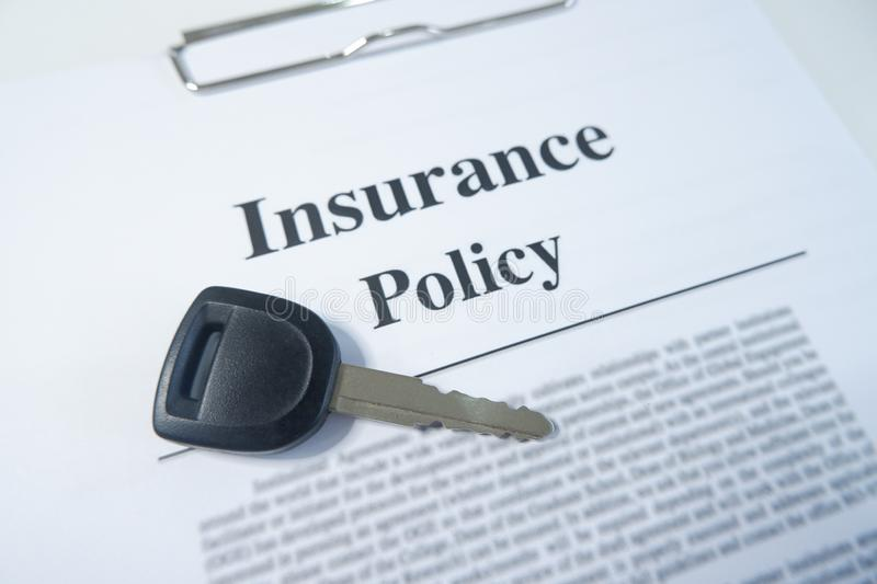 Close-up insurance policy, contract with car key on table stock image