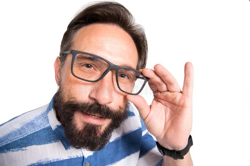 Close up of intelligent bearded man looking at you through glasses. Interrogative glance of smart mature man looking at you while touching the rim of his glasses royalty free stock photo