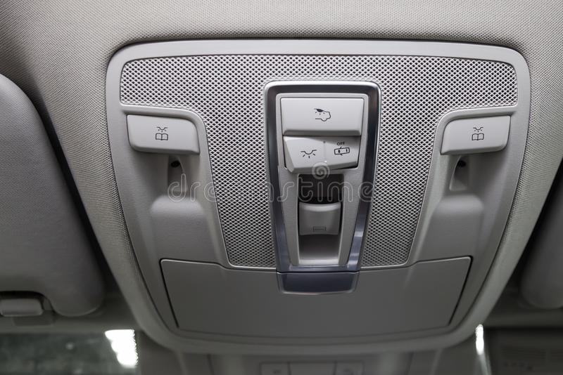 Close-up Interior view with roof light control dashboard and sunroof buttons of luxury very expensive new white car suv stands. After cleaning in the vehicle stock photography