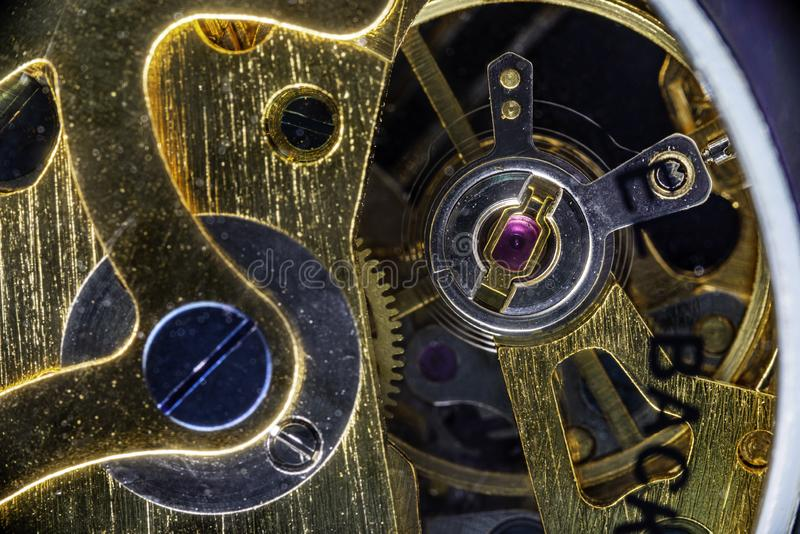 Close-up of the internal mechanism of a vintage analog self-winding watch. Focusing on the pink quartz crystal. Some internal reflections from dust speckles stock photography