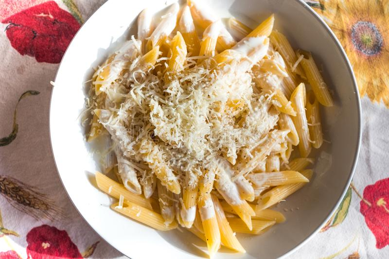 Close up of inviting penne pasta dish with cream and grated parmesan cheese on table with cloth royalty free stock photo