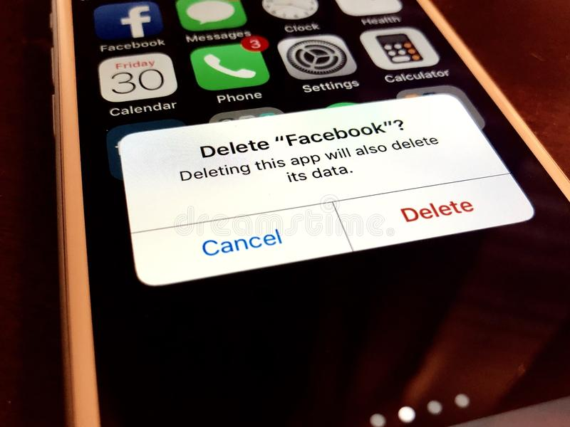 Deleting facebook app. Close up of an iphone with the option to delete the facebook app on the screen royalty free stock image