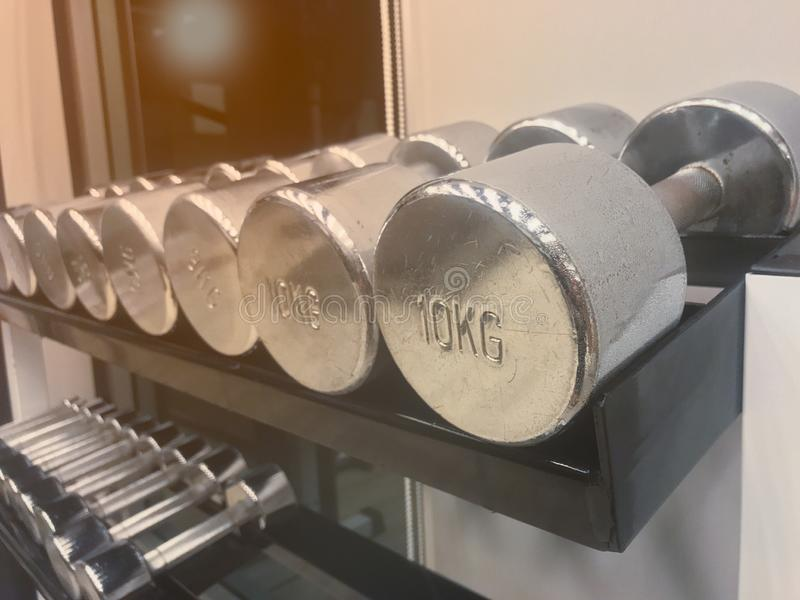 Close up Iron dumbbell have slightly rusted for workout on shelf stock photo