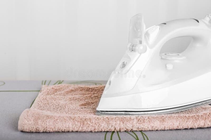 Close up of iron on ironing board.  royalty free stock image