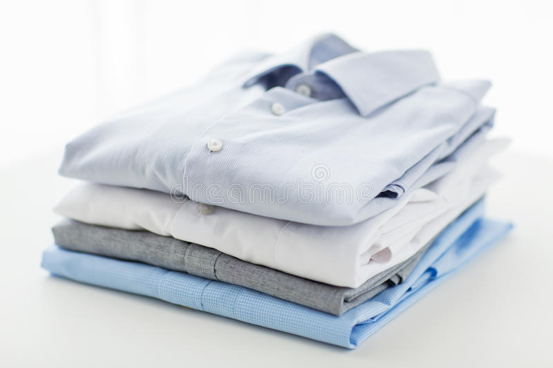 Close up of ironed and folded shirts on table. Ironing, laundry, clothes, housekeeping and objects concept - close up of ironed and folded shirts on table at stock photography
