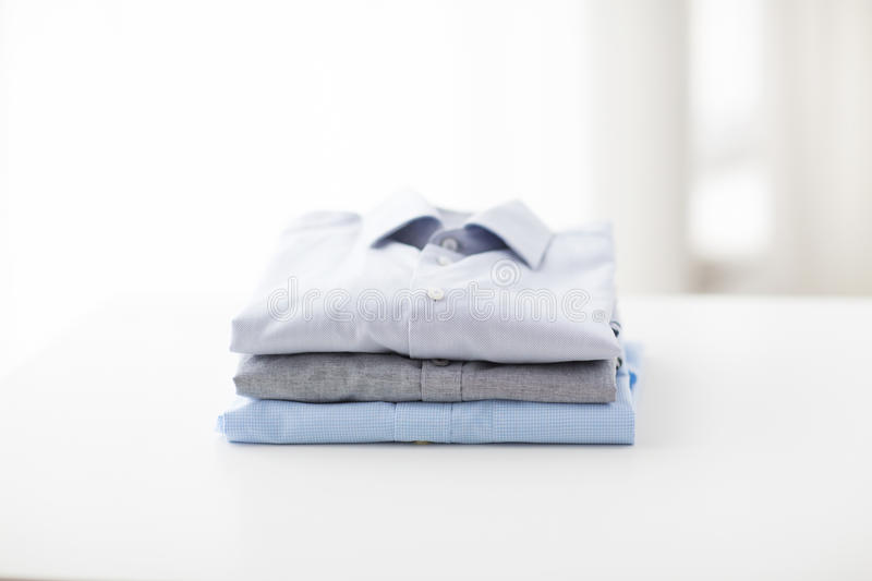 Close up of ironed and folded shirts on table. Ironing, laundry, clothes, housekeeping and objects concept - close up of ironed and folded shirts on table at royalty free stock images