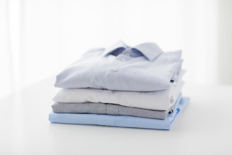 Close up of ironed and folded shirts on table. Ironing, laundry, clothes, housekeeping and objects concept - close up of ironed and folded shirts on table at royalty free stock photography