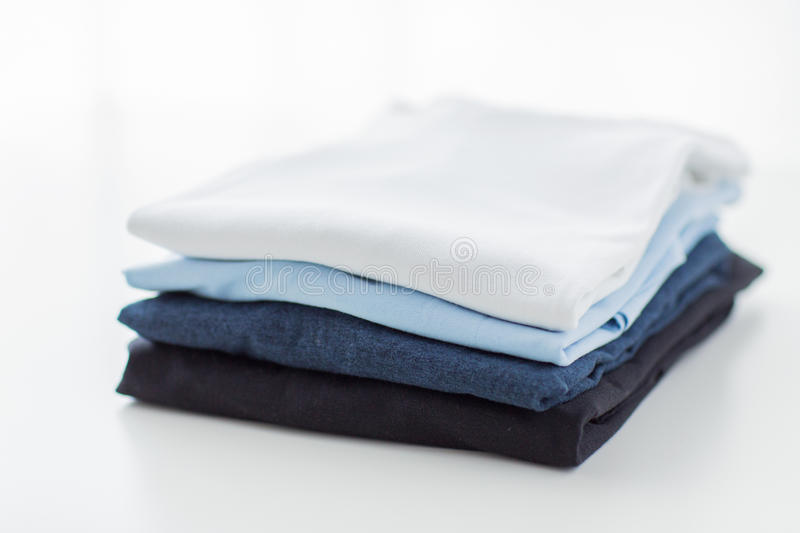 Close up of ironed and folded t-shirts on table. Ironing, laundry, clothes, housekeeping and objects concept - close up of ironed and folded t-shirts on table at stock photo