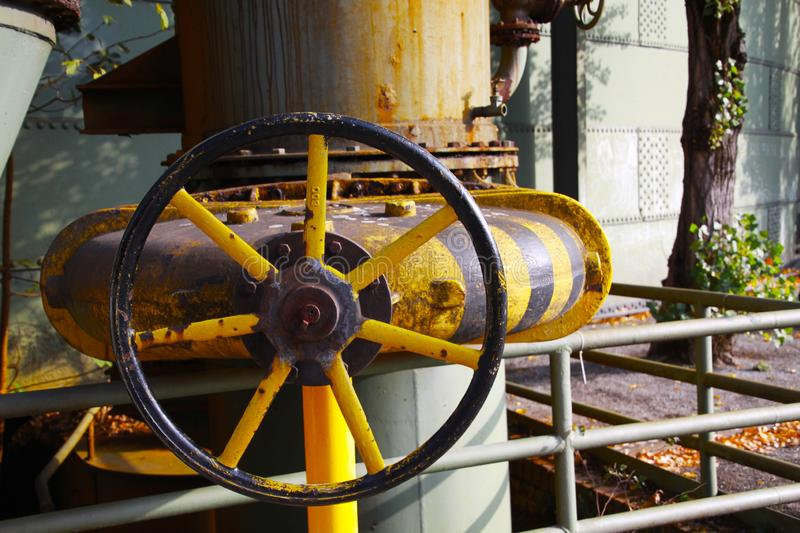 Landschaftspark Duisburg, Germany: Close up of isolated black and yellow striped rusty old wheel of control valve royalty free stock photos