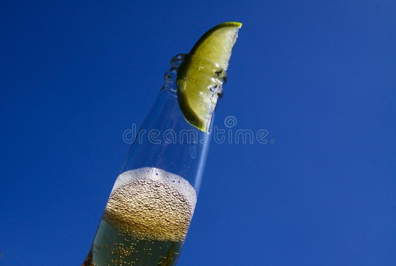Close up of isolated bottleneck with sparkling yellow beer and a slice of lime against cloudless deep blue sky. Germany stock images