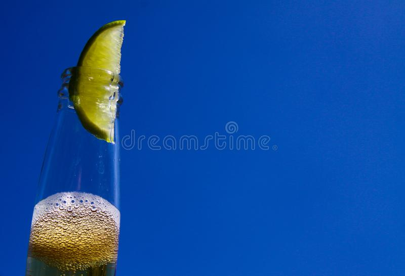 Close up of isolated bottleneck with sparkling yellow beer and a slice of lime against cloudless deep blue sky. Germany royalty free stock images