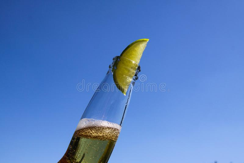 Close up of isolated bottleneck with sparkling yellow beer and a slice of lime against cloudless deep blue sky royalty free stock photos
