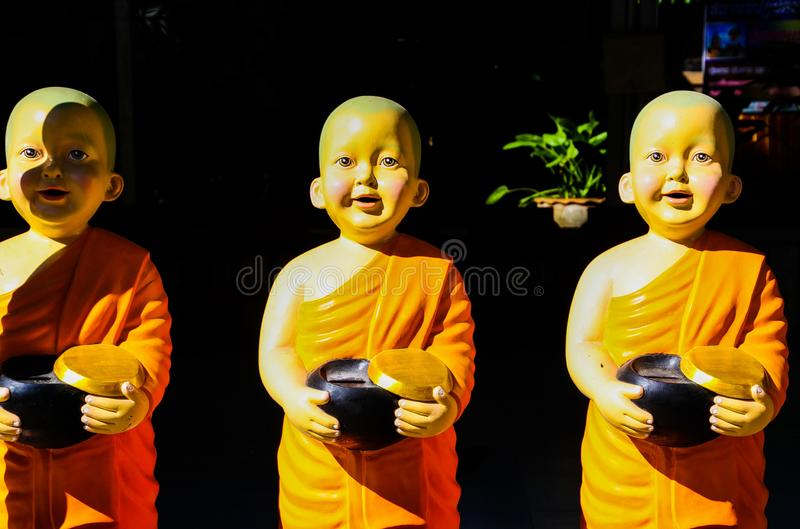 Close up of isolated bright shining sculptures of three happy young boy novice monks stock photography