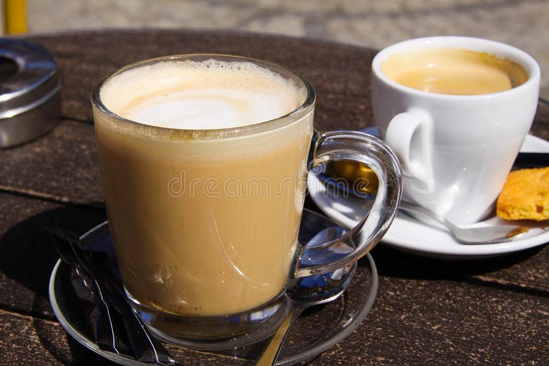 Close up of isolated brown dutch milk coffee koffie verkeerd in transparent glass mug and white espresso cup stock photography