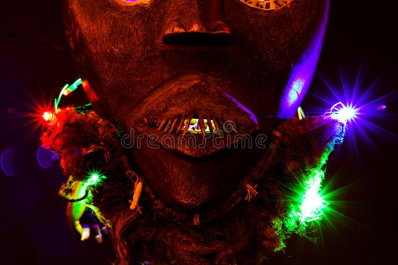 Close up of isolated colorful illuminated spooky african wood mask. Black background with vibrant bokeh stock image