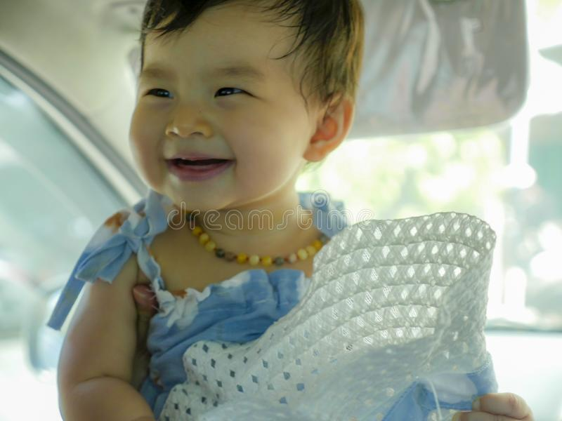 Close up isolated face portrait of sweet and adorable Asian Korean baby girl laughing and smiling cheerful holding hat enjoying royalty free stock image