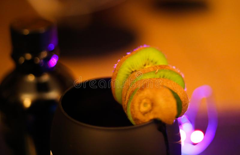 Close up of isolated kiwi fruit slices on black cocktail glass. Blurred bottle background. Focus on second slice royalty free stock photo
