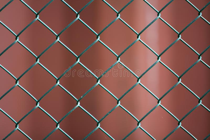 Close-up of isolated painted simple geometric black iron metal wire chain link fence eon dark red background. Fence, protection an. D enclosure concept royalty free stock image