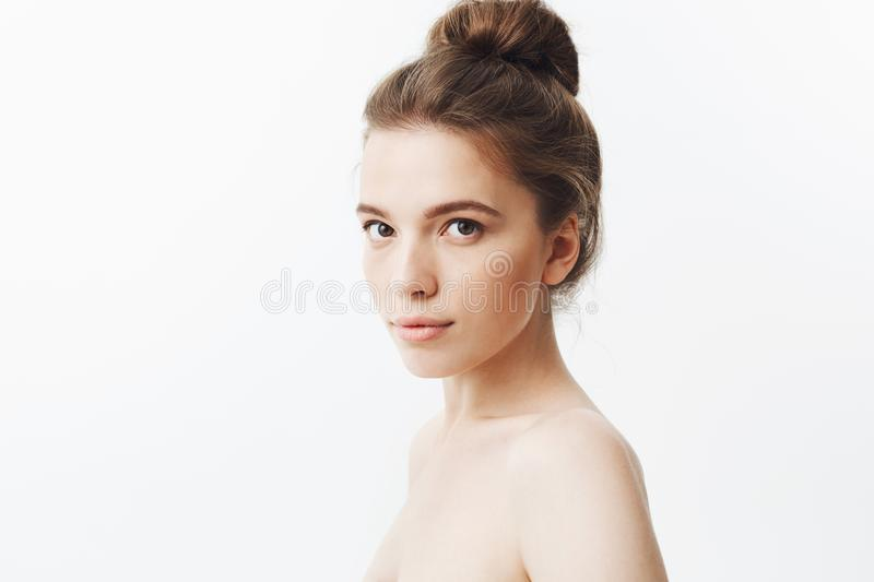 Close up isolated portrait of relaxed beautiful young skinny woman with long dark hair in bun hairstyle, posing half stock photography