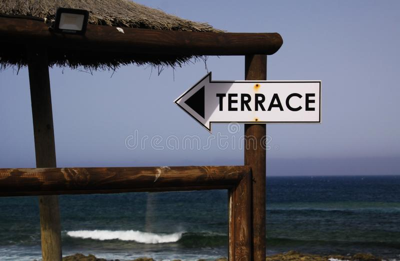 Close up of isolated terrace direction sign on wooden pole with ocean, blue sky and waves background - El Golfo, Lanzarote royalty free stock photo