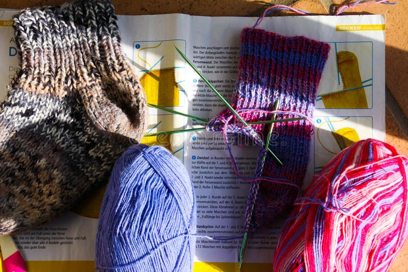 Close up of isolated two knitted socks on german magazine with needlework instruction, knitting needles and two colorful wool ball stock photo