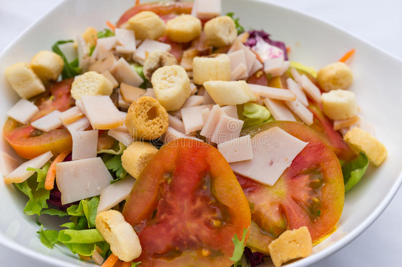 Close up of italian organic mixed vegetable salad with ham and t stock photo