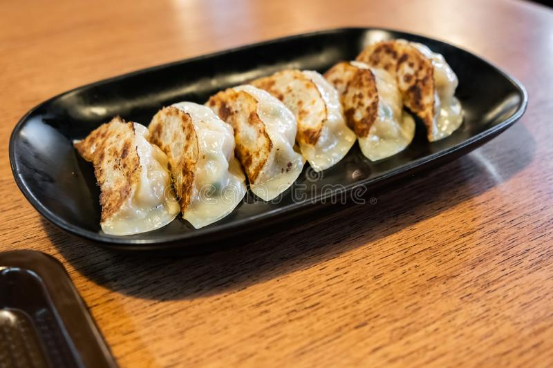 Close up Japanese dumplings- called Gyoza or Jiaozi in China, Gyoza with pork meat and vegetables. On black plate royalty free stock photography
