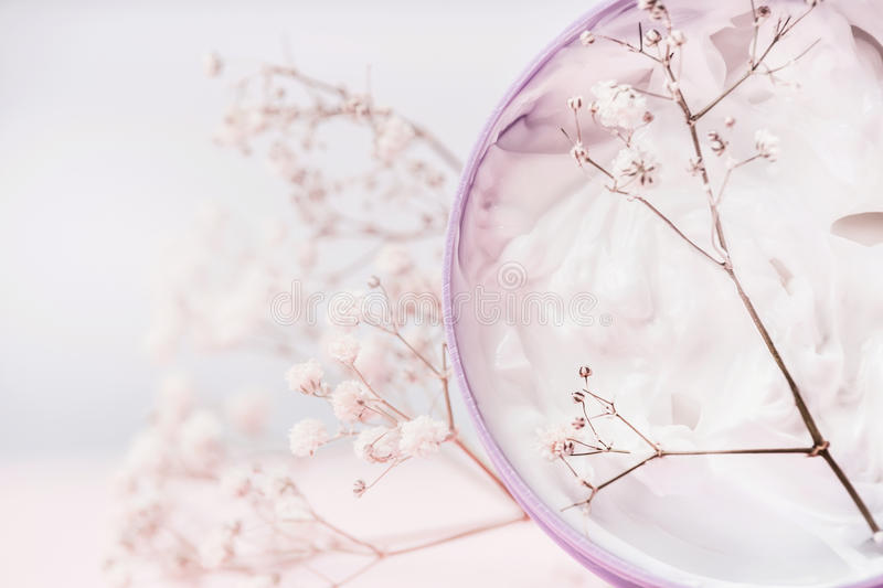 Close up of Jar with cosmetic cream and flowers , natural cosmetic product or beauty concept on pastel background stock image