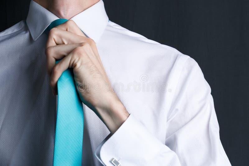 Close-up jonge mens in een wit overhemd met een band De man maakt zijn band, zijn ongeschoren recht gezicht Zakenman in een wit o stock afbeelding