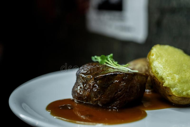 Close-up juicy grilled steak meat with barbecue sauce and stuffed potatoes on a plate in a restaurant. Healthy hot lunch. stock photography