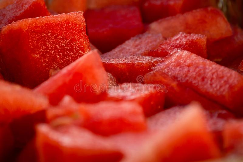 Close up of juicy red watermelon fruit that has been cut into cubes chunks stock image