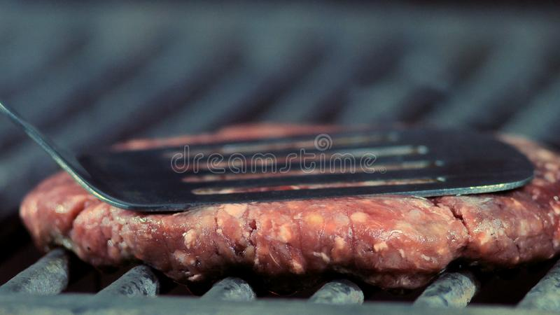 Close up of juicy round burger cutlet pressed to a grill with an iron spatula royalty free stock photography