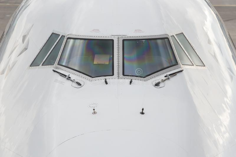 Close up of a jumbo jet nose, front view with windshield and wipers. royalty free stock photo