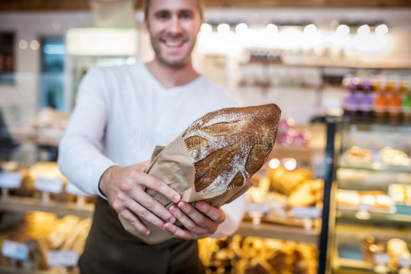 Close up of just baked rye bread in hands of man owning bakery. Baked rye bread. Close up of just baked rye bread in hands of successful young man owning bakery royalty free stock image