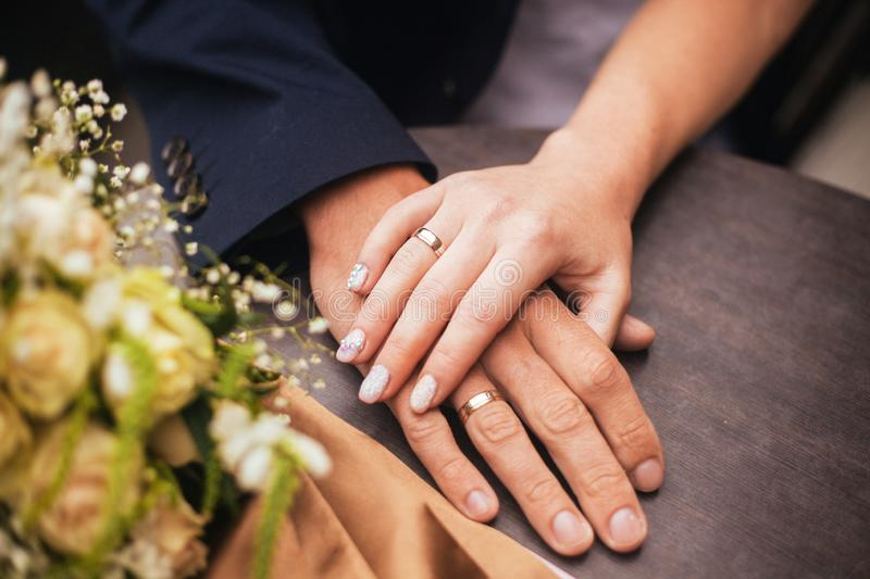 Close up of just married couple holding hands with rings and wedding bunch of flowers stock image