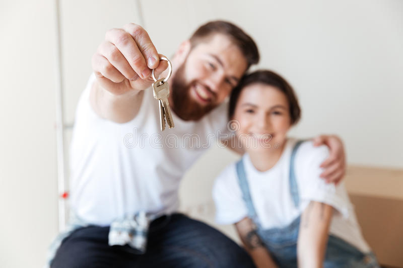 Close up of keys that showing young happy lovers. Isolated royalty free stock image