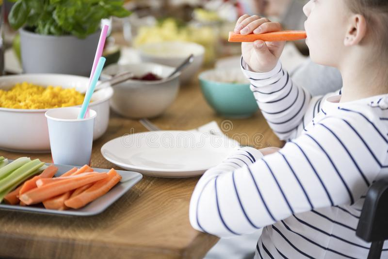 Close-up of kid eating carrot during breakfast. Healthy diet for royalty free stock photos
