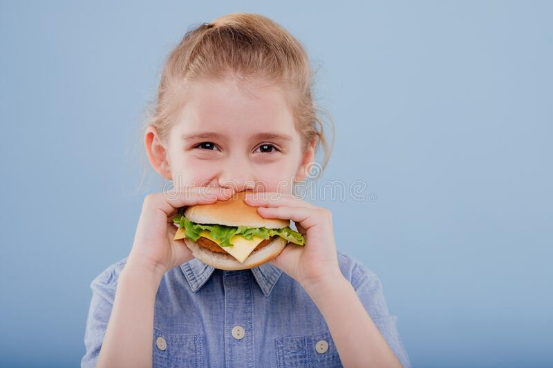 Close up, kid eats a sandwich. profile view, royalty free stock photography