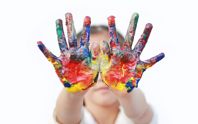 Close up kid hands painted in colorful paints isolated over white background royalty free stock photo