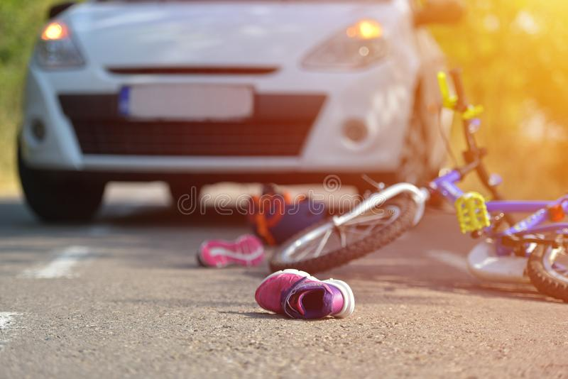 Close-up of a kid shoe fallen on the asphalt next to a bicycle a royalty free stock images