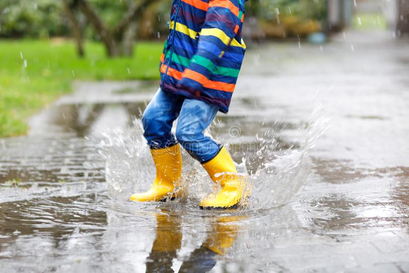 Close-up of kid wearing yellow rain boots and walking during sleet, rain and snow on cold day. Child in colorful fashion royalty free stock images