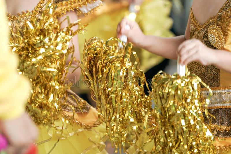 Close up kids` hand shake Glitter gold ribbon to cheer up their yellow sport team royalty free stock images