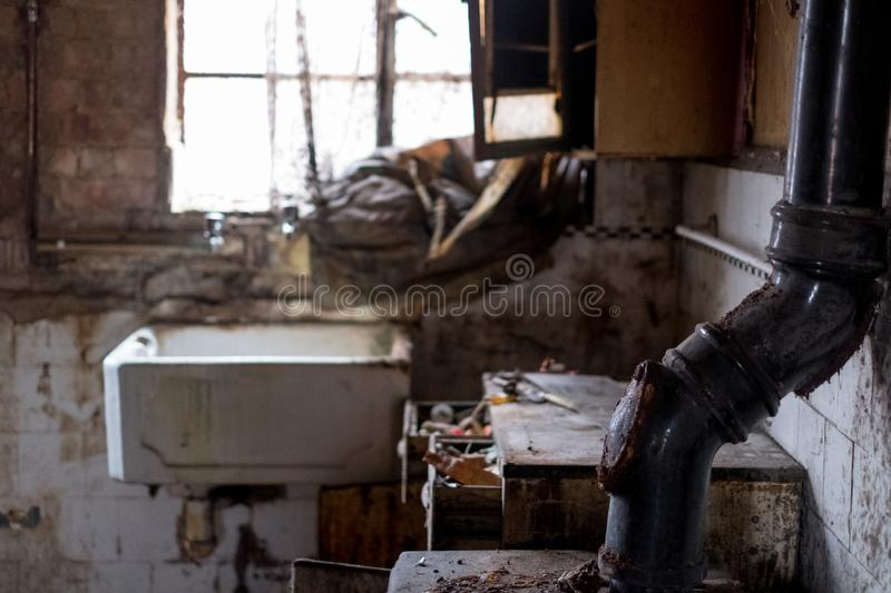 Close up of kitchen left in appalling condition in derelict 1930s deco house. Rayners Lane, Harrow UK. Close up of kitchen left in appalling condition in stock image