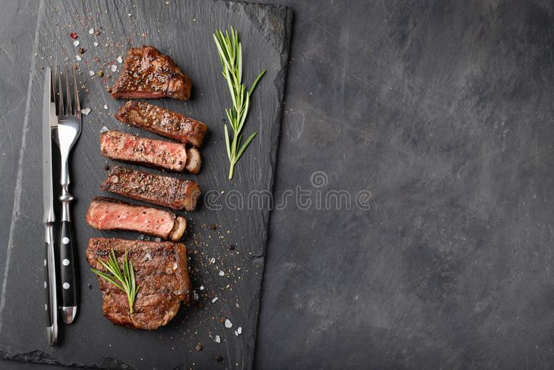 Close-up klaar om het rundvleesrassen van lapje vleesnew york van zwarte Angus met kruiden, knoflook en boter op een steenraad te royalty-vrije stock fotografie