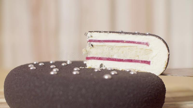 Knife taking out the piece of cake with silver droplets. Close up knife taking out the piece of cake with silver droplets royalty free stock images
